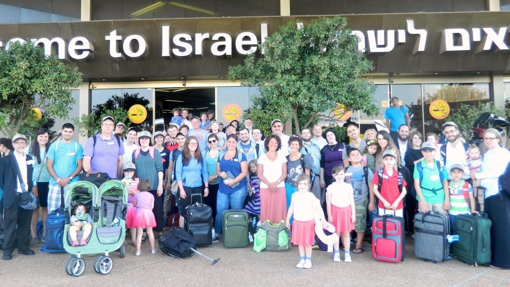 A group photo of the 64 olim who arrived in Israel Tuesday, July 8, 2014, after the commencement of Operation Protective Edge in the Gaza Strip.  (photo credit: Sasson Tiram/Nefesh B'Nefesh)