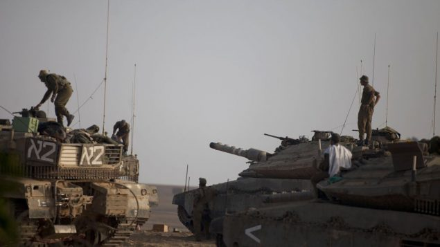 Israeli soldiers prepare their tanks near the Gaza border. Getty Images
