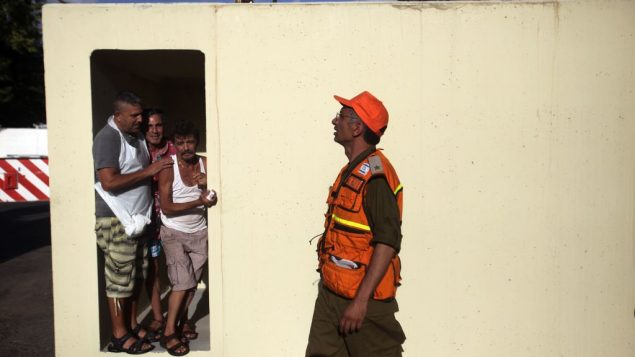 Israelis check a new bomb shelter as it's placed by a crane in the southern Israeli port city of Ashdod. Getty Images