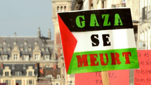 A protester holds a placard reading 'Gaza is dying' during a demonstration in Lille, France on July 19. Getty Images