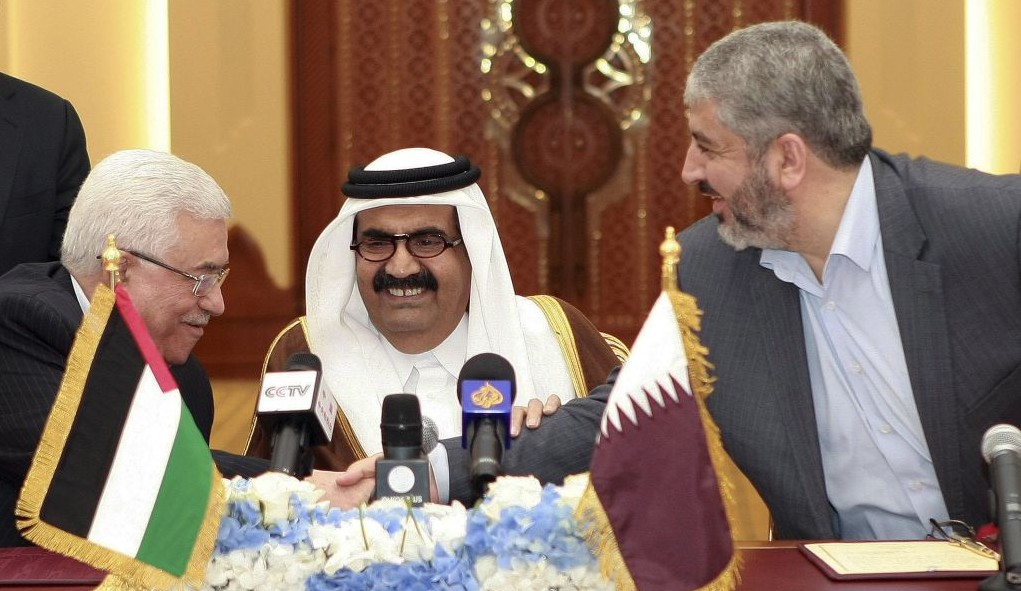 Palestinian President Mahmoud Abbas, left, shakes hands with Hamas leader Khaled Mashaal, right, as the Emir of Qatar, Sheikh Hamad bin Khalifa Al Thani, center, looks on, after signing an agreement in Doha, Qatar, Monday, Feb 6, 2012 (photo credit: AP/Osama Faisal)