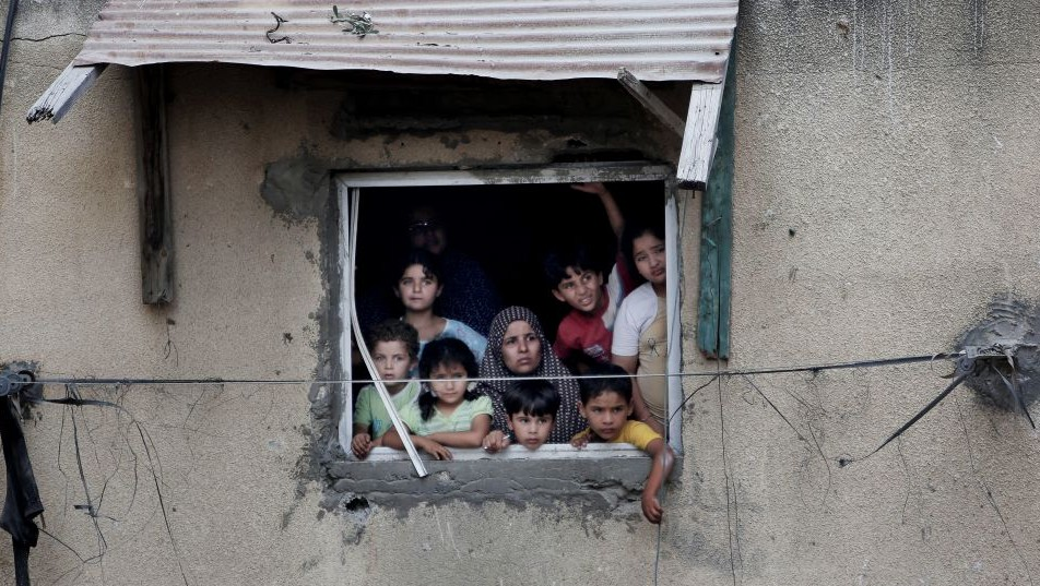 A Palestinian family watch rescuers searching for bodies and survivors under the rubble of a homes which were destroyed by an Israeli missile strike, in Gaza City, Monday, July 21, 2014. (Photo credit: AP/Khalil Hamra)