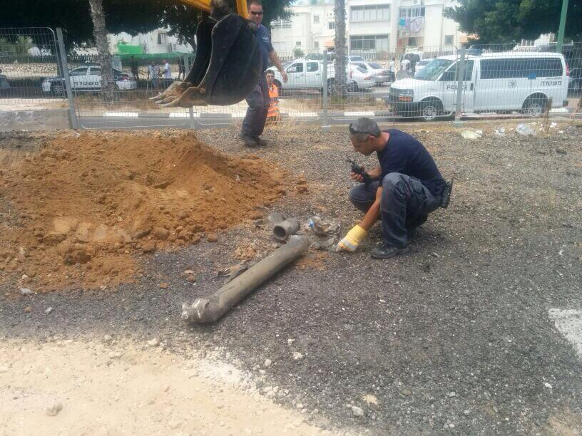 Sappers examine a rocket fired at the coastal city of Ashkelon, Sunday, July 13, 2014 (photo credit: Israel Police/Twitter)