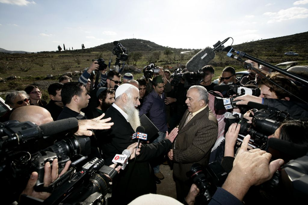 The late Rabbi Menachem Froman (L), a leader of the settler peace activist movement, meets with Palestinians at roadblock outside the West Bank village of Yasuf, in December 2009, to apologize for an act of vandalism in a village mosque (photo credit: Abir Sultan/Flash 90)