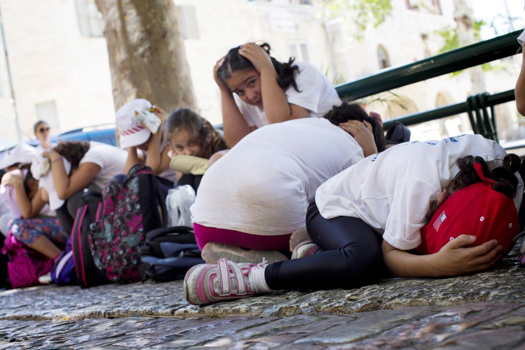 Illustrative photo of schoolchildren taking cover as part of an IDF Home Front Command drill simulating a bomb attack, May 27, 2013 (photo credit: Sarah Schuman/ Flash90)