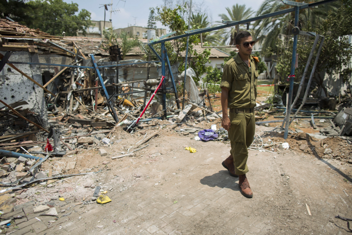 An Israeli soldier looks at the damage to a house following a rocket attack from the Gaza Strip on the town of Yehud, near Tel Aviv, on July 22, 2014. (photo credit: Yonatan Sindel/Flash90)