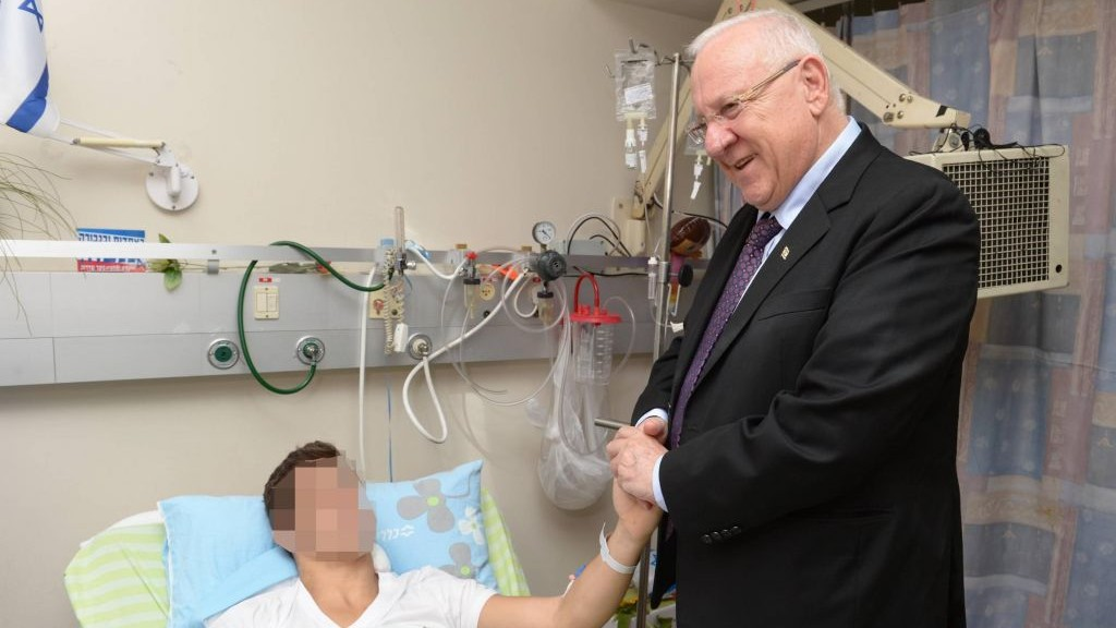 President Reuven Rivlin pays a visit to a soldier wounded in Operation Protective Edge, Monday, July 28, 2014. (photo credit: Mark Neiman/GPO)