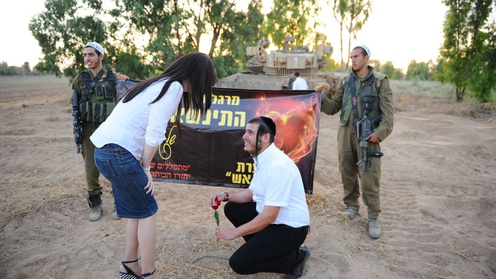 Berale Yackobovitz goes to his knees to propose to Margalit near a tank near the border with Gaza in South Israel, during Operation Protective Edge, July 15, 2014. (photo credit: Mendy Hechtman/Flash90)