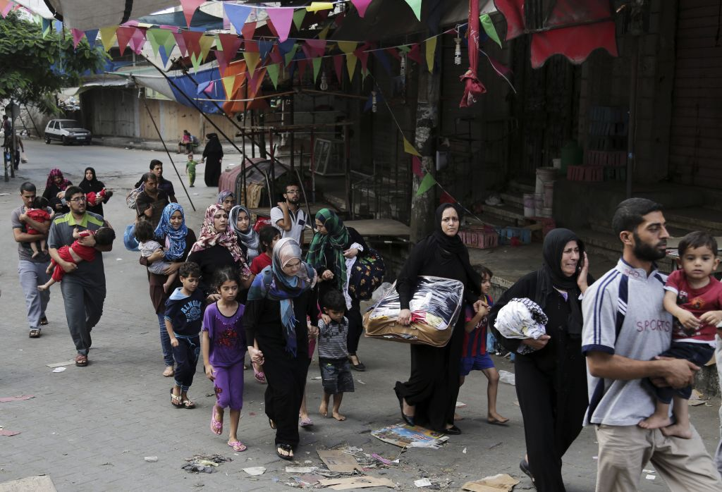 Palestinian families who fled their homes from Shejaiya neighborhood, arrive to Gaza City, northern Gaza Strip on Sunday, July 20, 2014. (photo credit: AFP/Adel Hana)