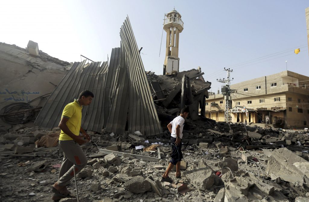 Palestinians gather around the ruins of the Al-Tawfeeq mosque, which Israel said concealed weapons, after it was hit by an Israeli missile strike in the Nuseirat refugee camp, central Gaza Strip, Saturday, July 12, 2014 (photo credit: AP/Hatem Moussa)