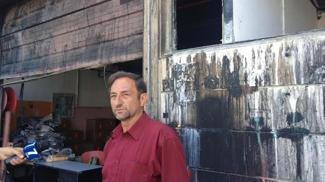 The owner of the Denber paint factory speaking on the backdrop of the factory, which was set aflame last Saturday (photo credit: Mitch Ginsburg/Times of Israel)