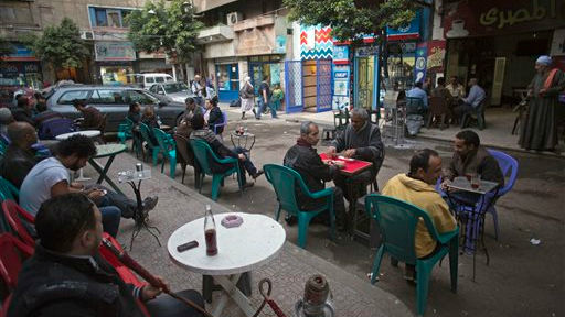 Egyptians sit in an outdoor cafe next to the Zawya cinema off the packed streets of downtown Cairo, March 19, 2014 (photo credit: AP/Khalil Hamra)