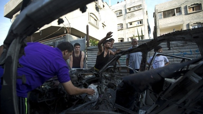 Palestinians inspect the wreckage of a car hit by an Israeli air strike, killing three people and wounding four others, early on July 10, 2014 in Gaza City. (photo credit: AFP PHOTO / MAHMUD HAMS)