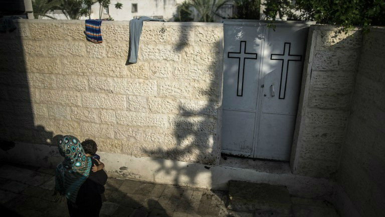 A Palestinian woman carrying an infant is pictured at the entrance of Gaza City's Greek Orthodox church compound on July 23, 2014 where around 600 people, mostly women and children, are sheltering (photo credit: AFP/Marco Longari)