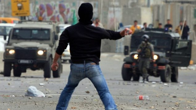 Palestinians throw stones at the Israeli police during clashes on Wednesday. Courtesy of timesofisrael.com