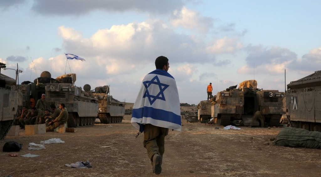 An IDF  soldier clad in an Israeli flag near the border with Gaza, July 19, 2014. (Photo credit: Nati Shohat/Flash90)