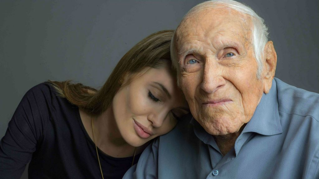 "Angelina Jolie is photographed with Louis Zamperini. Zamperini, a US Olympic distance runner and World War II veteran who survived 47 days on a raft in the Pacific after his bomber crashed, then endured two years in Japanese prison camps. Jolie directed the Universal movie, ""Unbroken,"" about the life of Zamperini. (photo credit: AP/Universal Pictures)"