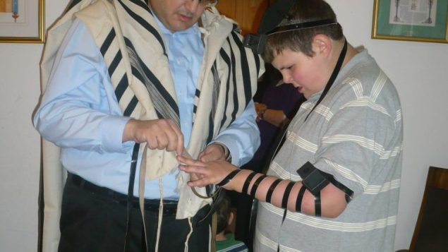 Avi puts on tefillin with his father. Courtesy of Michelle Steinhart