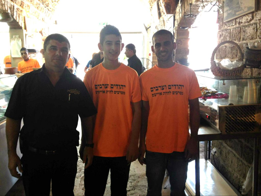 Hani Harawi, the long-time manager of Aboulefia, a family-owned restaurant and bakery, whose staff are wearing shirts stating their commitment to coexistence in Jaffa (photo credit: Jessica Steinberg/Times of Israel)