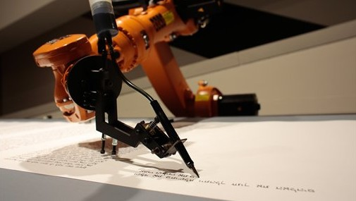 A robot writes a Torah at an installation in the Jewish Museum in Berlin, Germany, on Thursday, July 10, 2014. (photo credit: AP/Markus Schreiber)