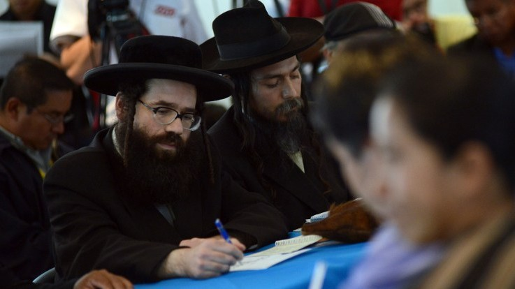 Members of the Orthodox Jewish community attend a meeting with leaders of San Juan La Laguna community at the headquarters of the Human Rights Office in Guatemala City on August 27,2014. (Photo credit: AFP / Johan ORDONEZ)