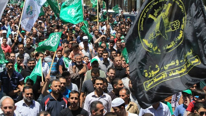 Palestinian protestors wave Hamas and Islamic Jihad flags as they take part in a demonstration is support of Gaza after Friday prayers in the West Bank town of Hebron on August 8, 2014. (Photo credit: AFP/HAZEM BADER)