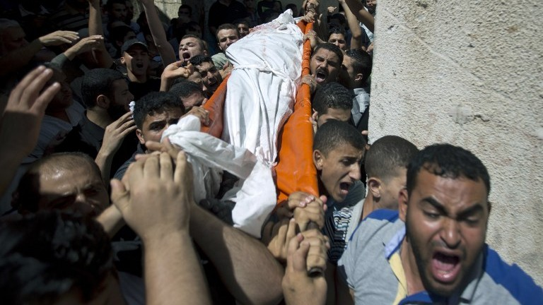 Palestinian mourners carry the body of one of three senior Hamas commanders during their funeral in the southern Gaza Strip town of Rafah, on August 21, 2014. (photo credit: AFP Photo/Mahmud Hams)