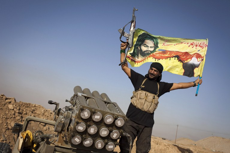 An Iraqi militia fighter of the Shiite cleric Muqtada al-Sadr's Saraya al-Salam (Peace Brigade), waves a flag next to a rocket launcher during heavy clashes with IS fighters in Tuz Khurmatu in the Salaheddin province on August 31, 2014. (photo credit: AFP/J.M. Lopez)