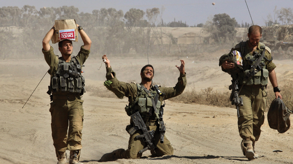 An Israeli soldier gestures in relief Monday near the border with Gaza as Israel began redeploying its troops. Getty Images