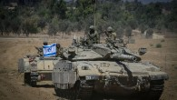 Israeli soldiers hold an Israeli flag on top of a tank