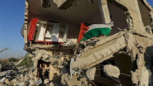 A Palestinian walks into a house, destroyed by an Israeli strike in the Gaza City neighborhood of Shejaiyah, a Hamas stronghold from which hundreds of rockets were fired at Israel, as