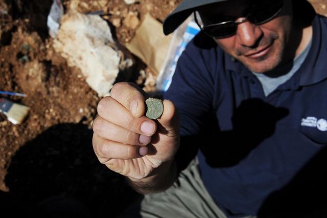 IAA archaeologist Pablo Betzer holds up a Jewish Revolt coin found outside Jerusalem. (photo credit: Vladimir Neichin, IAA)