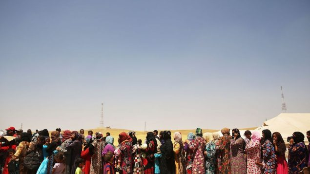 Iraqi women queue up at a displaced persons camp near Mosul. Getty Images