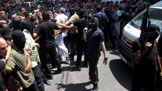 Armed Palestinian masked militants attempt to control the crowd before the execution of alleged collaborators. Getty Images