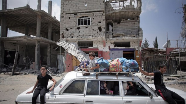 Palestinians in a car with their belongings drive past a destroyed house in Rafah's district of Shawkah in the southern Gaza Strip, Tuesday, Aug. 5, 2014. (photo credit: AP/Khalil Hamra)