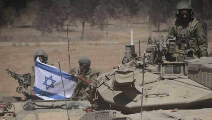 Israeli soldiers display the flag near the Gazan border, Aug. 1, 2014. (photo credit: Albert Sadikov/Flash90)