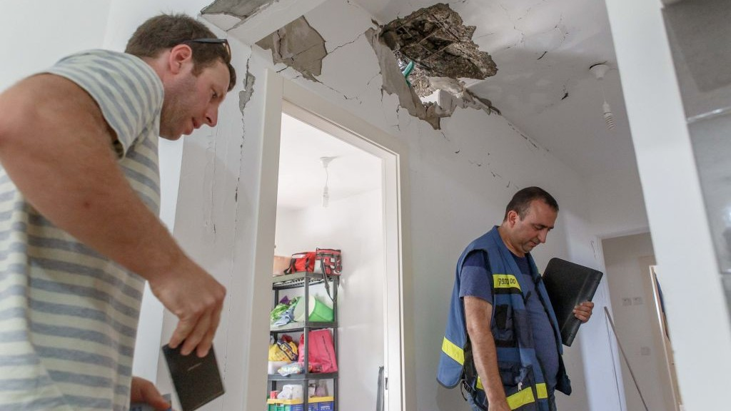 Tax authority workers survey the damage caused to a house after it was hit by a rocket in the Ashkelon Regional Council, on August 20, 2014. (photo credit: Flash90)