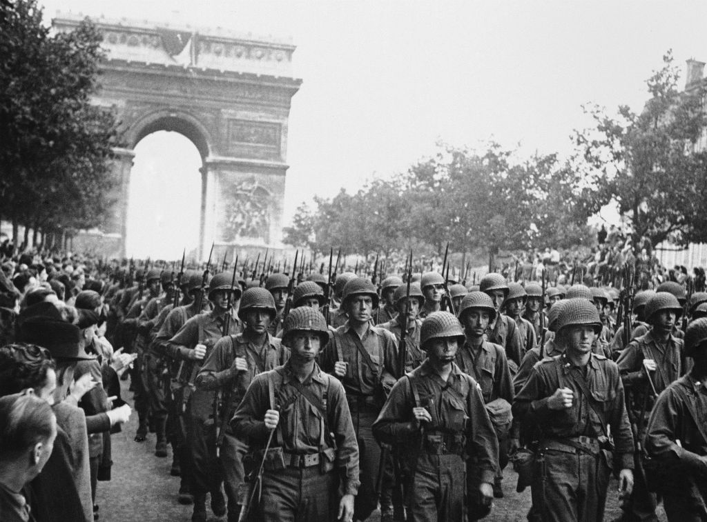 In this photo provided by the U.S. Office of War Information, American troops march down the Champs Elysees, past the Arc de Triomphe, Sept. 12, 1944, as residents of Paris throng the sidewalks to cheer following the liberation of Paris on August 25, 1944. (photo credit: AP Photo/Richard Boyer, U.S. Office of War Information)