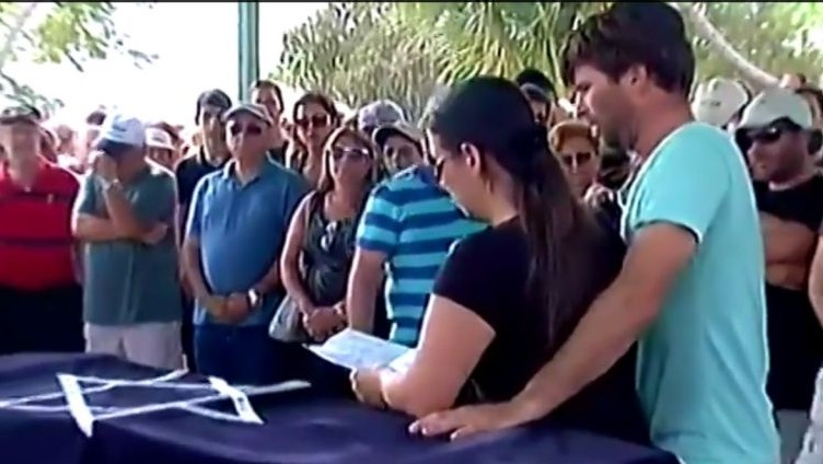 Gila Tragerman, with her husband Doron at her side, speaks at the August 24 funeral of their son Daniel, 4, killed August 22 at Kibbutz Nahal Oz by a mortar shell fired from Gaza. (YouTube screenshot)