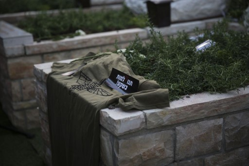 The grave of IDF soldier Lee Matt, seen during the vigil ceremony at the Mount Herzl Military Cemetery in Jerusalem, August 21, 2014. A sticker on his grave, which reads 'Let me die in peace,' was made by his family as a protest against army regulations on what gets written on the soldier's tombstone. (photo credit: Hadas Parush/Flash90)