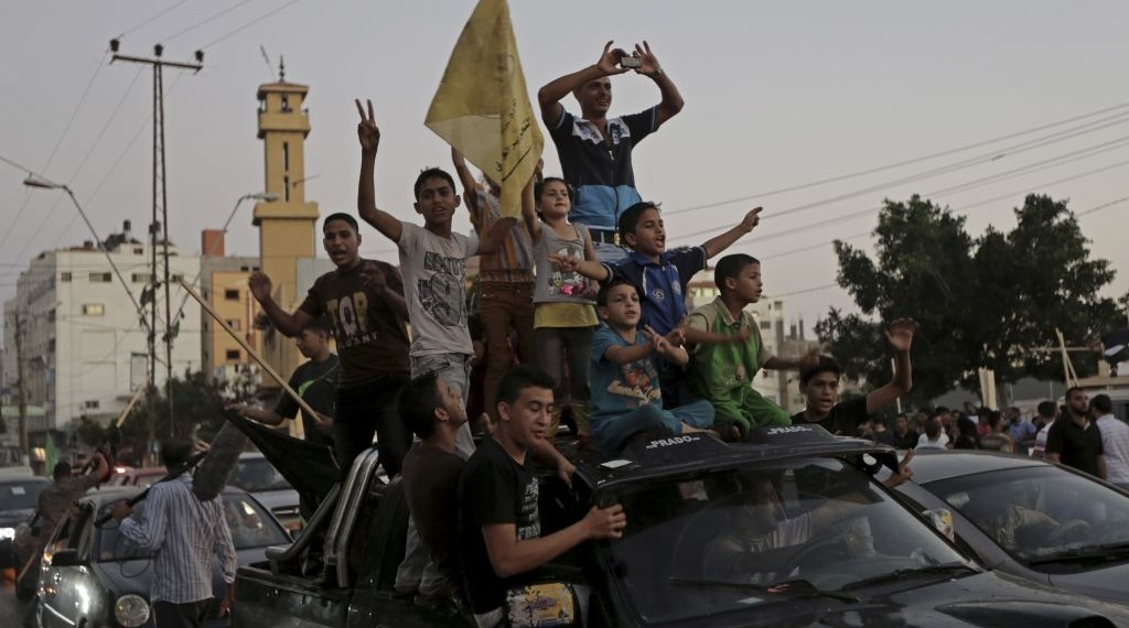 Gazans celebrate the Israel-Hamas ceasefire, in the northern Gaza Strip, Tuesday, Aug. 26, 2014.  (photo credit: AP Photo/Adel Hana)