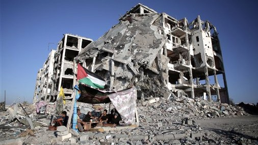 In this Monday, Aug. 11, 2014 file photo, Palestinian Ziad Rizk, sits with others in a shelter made of a blanket stretched over four poles next to one of the destroyed al-Nada Towers, where he lost his apartment and clothes shop, in the town of Beit Lahiya, northern Gaza Strip.  (photo credit: AP Photo/Khalil Hamra, File)