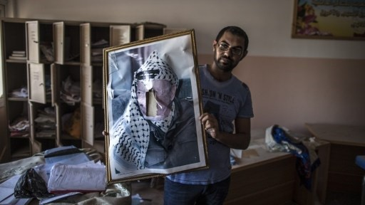 A defaced portrait of the late Palestinian leader Yasser Arafat is held by a man in a classroom after Israeli soldiers withdrew from the Beit Hanun High school for girls which was reportedly used as an advanced base during Israel's military offensive against the Hamas-held Gaza Strip, on August 5, 2014.  (photo credit: MARCO LONGARI / AFP)