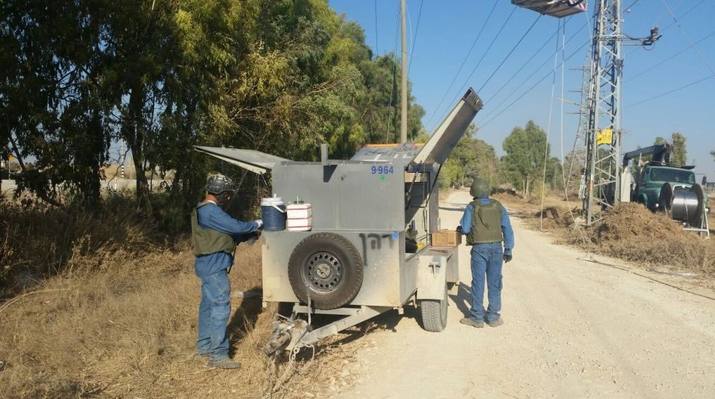IEC employees fix power lines on the Gaza border, wearing helmets and armored vests (photo credit: Charlie‎ Shriki, Courtesy of the Israel Electric Corporation)
