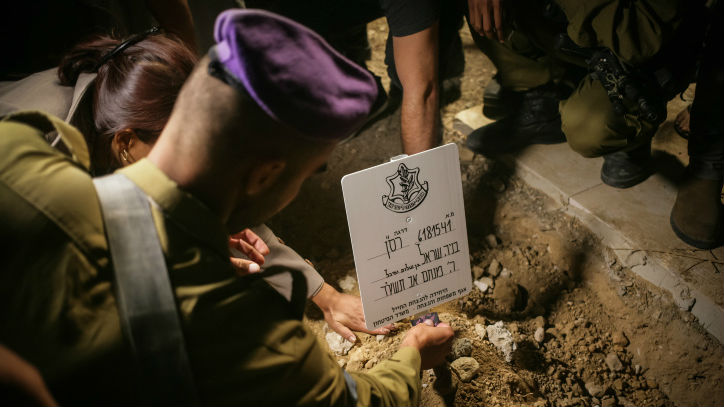 Relatives and friends seen mourning over the grave of Major Benaya Sarel, during his funeral at the old Jewish cemetery in Hebron on August 3, 2014. (photo credit: Flash90)