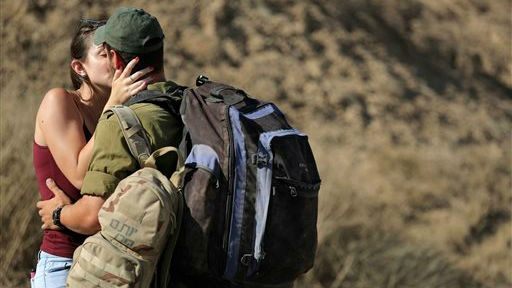 An Israeli soldier kisses his girlfriend before he returns to his unit in a staging area near the Israel Gaza border, Saturday, August 2, 2014 (photo credit: AP/Tsafrir Abayov)