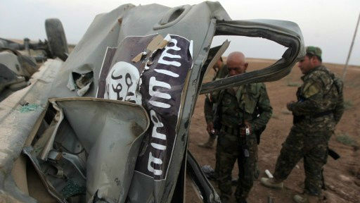 Peshmerga fighters inspect the remains of a car, bearing an image of the trademark jihadist flag, which belonged to Islamic State (IS) militants after it was targeted by an American air strike in the village of Baqufa, north of Mosul, on August 18,2014 (photo credit: AFP/Ahmad al-Rubaye)