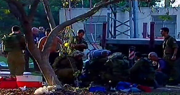 First responders and IDF soldiers at the scene of a mortar barrage on Kibbutz Nirim in the Eshkol region. (screen capture: Channel 2)