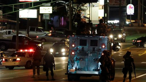 Police attempt to secure a street after a clash with protesters Wednesday, Aug. 13, 2014, in Ferguson, Mo. (photo credit: AP/Jeff Roberson)
