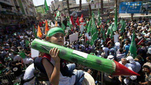 A Palestinian boy, along with supporters of Hamas, holds a representation of a rocket as others shout slogans to protest against Israel and to support people in Gaza, during a demonstration in the West Bank city of Ramallah, Friday, Aug. 22, 2014 (photo credit: AP /Majdi Mohammed)